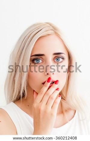 Surprised upset girl covers her mouth and her eyes wide open. A conceptual photo on a white background - stock photo