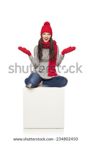 Surprised winter woman wearing knitted warm red scarf and hat sitting on big white box, over white background - stock photo