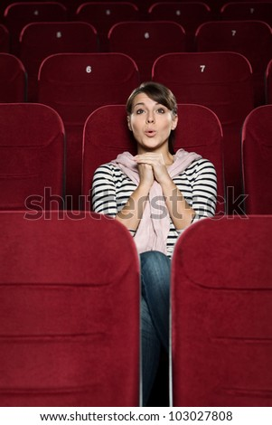 Surprised woman at the cinema - stock photo