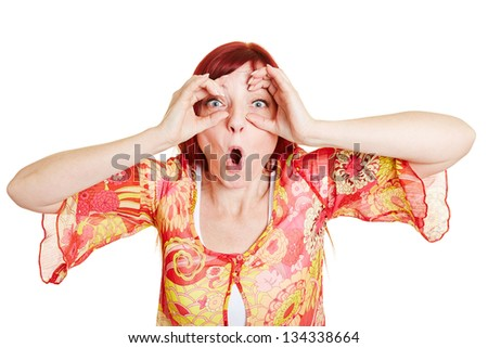 Surprised woman holding her fingers around her eyes - stock photo