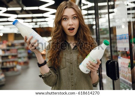 Surprised woman in green shirt choosing a milk in supermarket