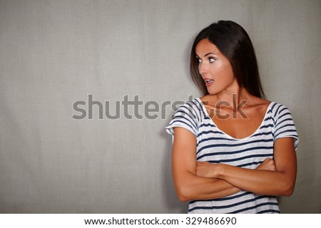 Surprised woman in her 30s standing with arms crossed - copy space