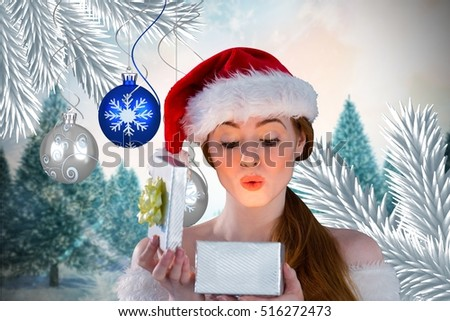 Surprised woman in santa hat looking at christmas gift against digitally generated background