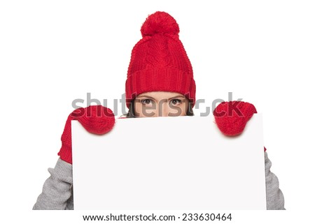 Surprised woman in winter hat peeking out of the edge of white banner and winking over white studio background - stock photo