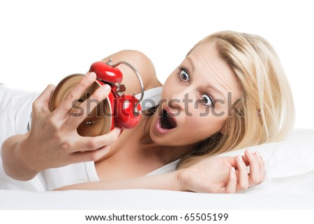 Surprised woman looking at alarm clock . - stock photo