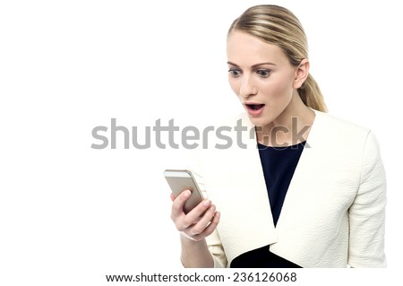 Surprised woman, looking at her mobile phone - stock photo