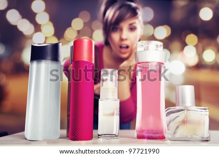Surprised woman looking at perfumes - stock photo