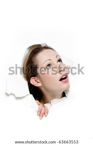 surprised woman looking up through hole in paper - stock photo