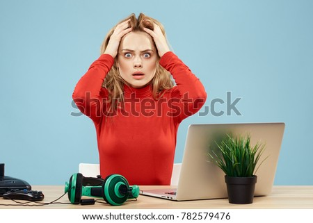 surprised woman on blue background, laptop, headphones, playstation