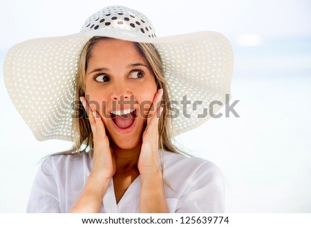 Surprised woman on holidays at the beach - stock photo