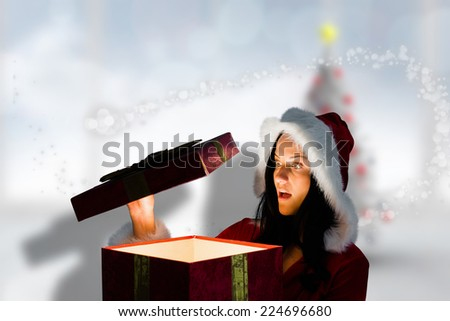 Surprised woman opening christmas present against blurry christmas tree in room - stock photo
