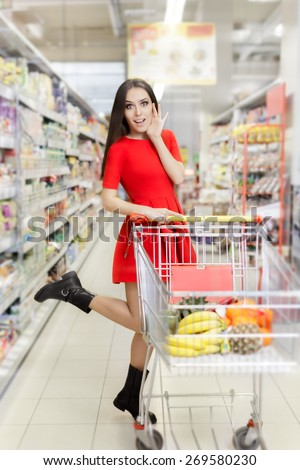 Surprised Woman Shopping  at The Supermarket - Portrait of a young girl in a market store with a shopping cart - stock photo