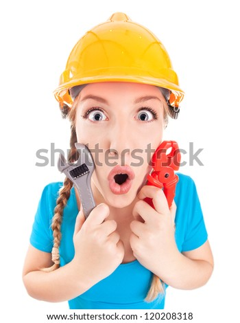 Surprised woman wearing a hardhat holding pliers and spanner - stock photo