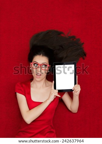 Surprised Woman Wearing Glasses Holding Tablet - Beautiful amazed woman in red decor holding a tablet PC  - stock photo