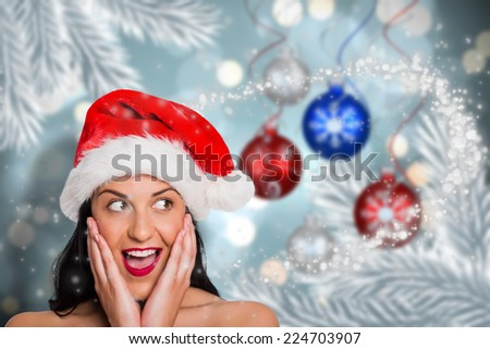 Surprised woman wearing santa hat against baubles hanging over christmas scene