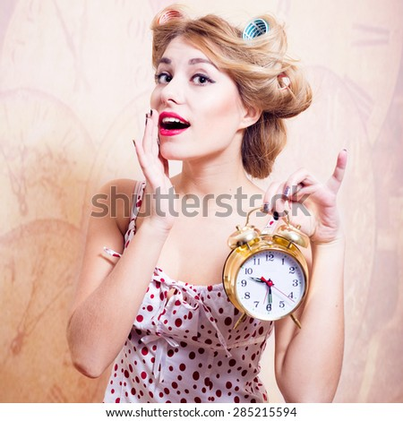 Surprised woman with alarm clock looking at camera - stock photo