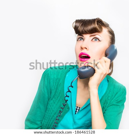 Surprised woman with open mouth and retro phone. Pinup girl. Beauty woman over white background. Emotions - stock photo