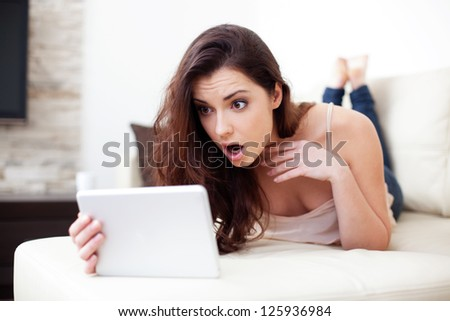 Surprised woman with tablet lying on couch - stock photo