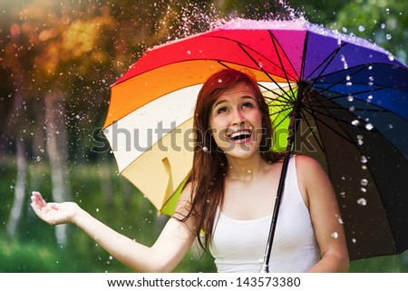 Surprised woman with umbrella during summer rain - stock photo