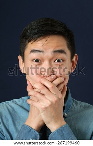 Surprised young Asian man covering his mouth with palms - stock photo