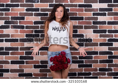 Surprised young beautiful woman with roses between her legs
