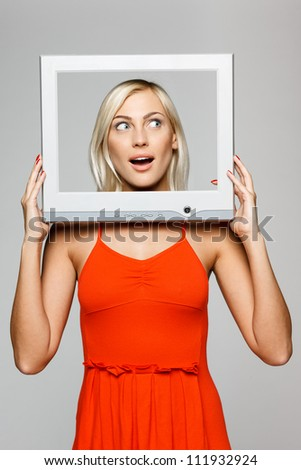 Surprised young blond female looking through the TV / computer screen frame, looking to the side, over gray background