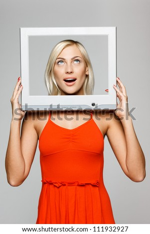 Surprised young blond female looking through the TV / computer screen frame, looking up, over gray background