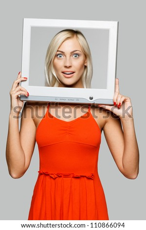 Surprised young blond female looking through the TV / computer screen frame, over gray background