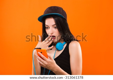Surprised young brunette woman, with blue headphones on her neck, wearing in black blouse and cap, holding smart phone in her hand - isolated on orange background, in studio, waist up - stock photo