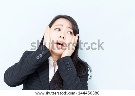 surprised young business woman against light blue background - stock photo