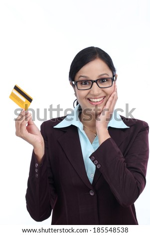 Surprised young business woman with credit card against white background - stock photo