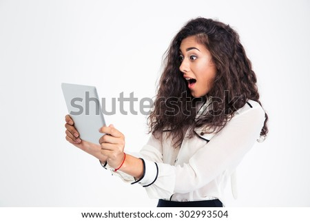 Surprised young businesswoman looking at tablet computer isolated on a white background - stock photo