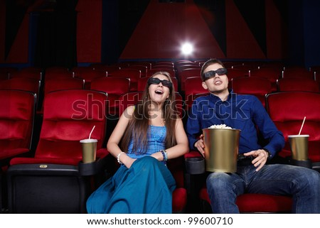 Surprised young couple in a movie theater - stock photo