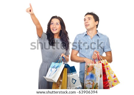 Surprised young couple with shopping bags looking up and pointing to copy space isolated on white background - stock photo