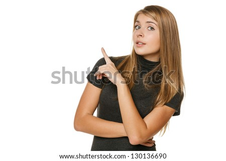 Surprised young female pointing to the side at copyspace over white background - stock photo