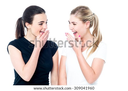 Surprised young girls laughing out loud over white - stock photo