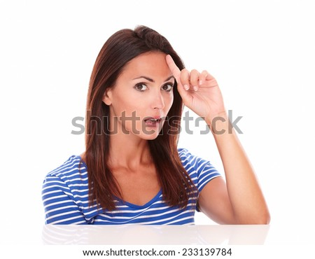 Surprised young lady pointing to her forehead while looking at camera in white background - stock photo