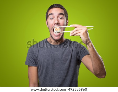 Surprised young man eating sushi on green background
