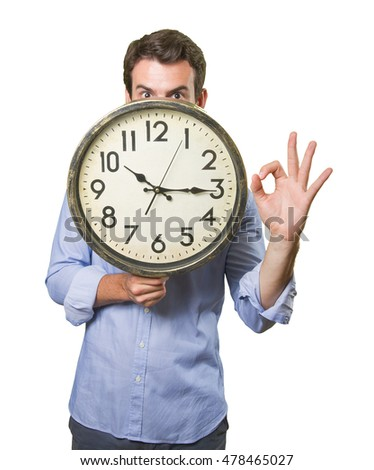 Surprised young man holding a clock on white background