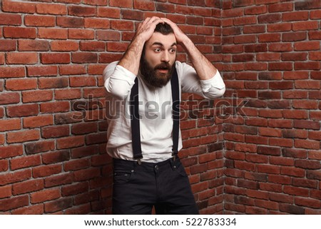 Surprised young man in suit with suspenders over brick background.