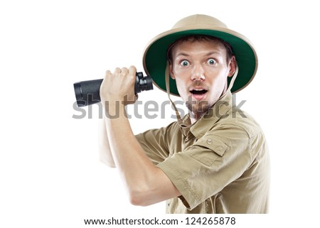Surprised young man wearing a pith helmet and holding binoculars, isolated on white - stock photo