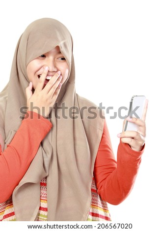 surprised young muslim girl looking at cell phone - stock photo