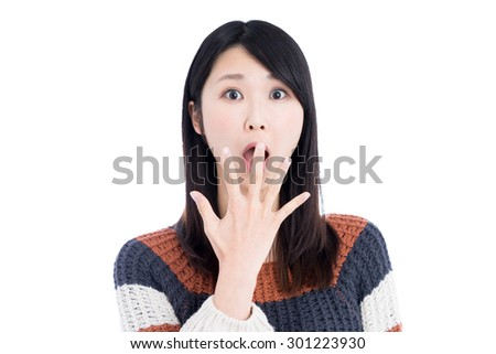 surprised young woman against light green background - stock photo