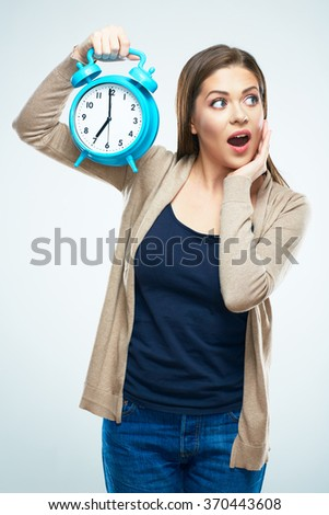 Surprised young woman hold alarm clock. White background isolated. - stock photo