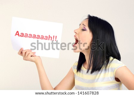 """Surprised young woman holds inscription """"ah"""" on grey background - stock photo"""