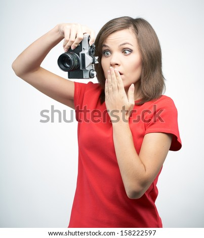 Surprised young woman in a red shirt. Holds the camera. On a gray background