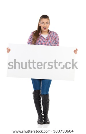 Surprised young woman in jeans, black boots and lumberjack shirt standing and holding white placard. Full length studio shot isolated on white. - stock photo