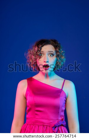 Surprised young woman looking at the camera. on blue backgraund - stock photo
