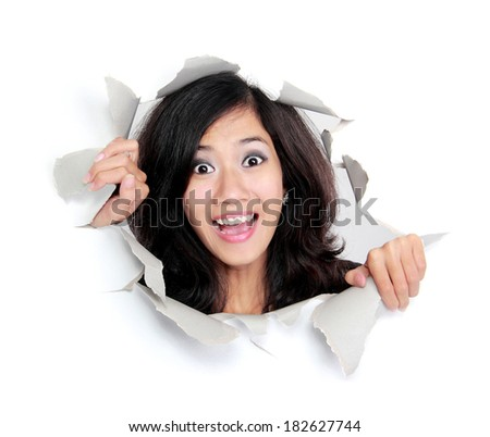 surprised young woman looking through a hole. Isolated on white background - stock photo