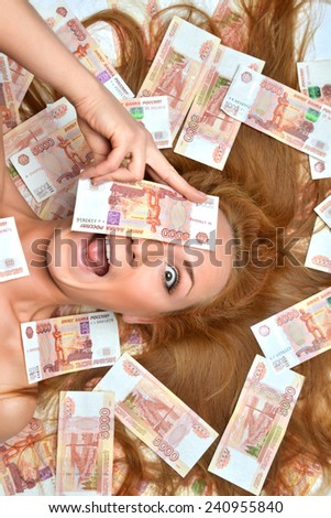 Surprised young woman lying down with many cash money five thousand russian rubles notes in hand looking at the camera isolated on a white background - stock photo